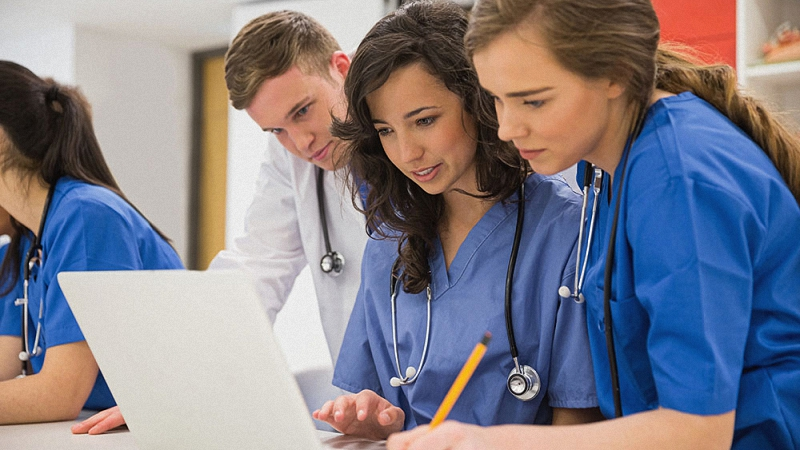 Medical students having a discussion while looking at a computer